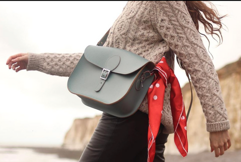 A cutoff picture of a blond woman with a blue satchel bag. The bag has a red handkerchief tied to one side.