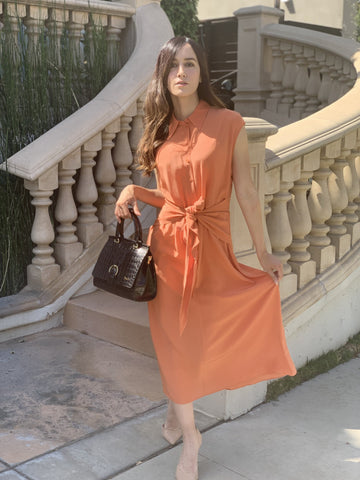 A woman in a light orange dress poses for the camera with a small black satchel bag.