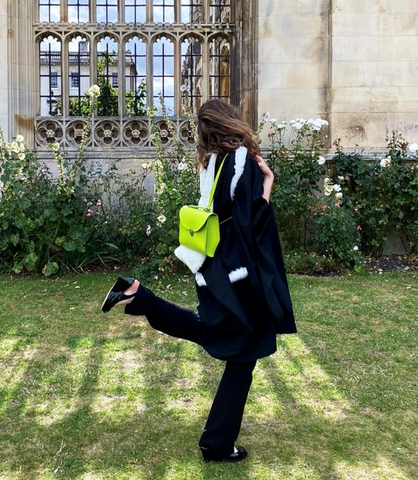 A woman dressed in black poses with her back to the camera, holding a bright yellow-green satchel bag.