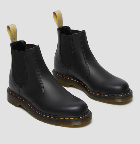 Black laceless workboots with thick rubber soles.