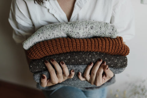 A close shot of a woman holding four thick knit sweaters. From top to bottom: a light speckled white, a dark orange, a dark grey with white dots, and a plain light grey.