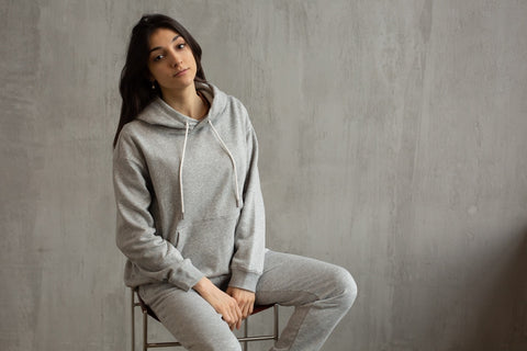 A woman in a grey sweatsuit sits in front of a grey background.