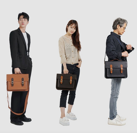 Three people - a man in a suit, a woman in jeans and a sweater, and an older man in light jeans and a dark shirt - carrying satchel bags in various colors.