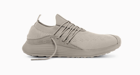 A tan-grey casual sneaker with laces across the middle. The upper appears to be made of mesh with leather accents.