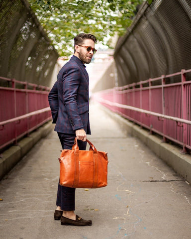 A man in a blue suit holds a light brown messenger bag as he poses on a concrete bridge.