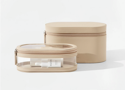 A set of two tan travel cases. In back, a plain zippered oval-shaped case. In front, a smaller zippered oval-shaped case with clear plastic sides and a clear plastic lid.