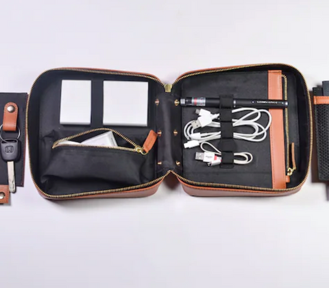 A brown tech organizer open to reveal a black interior stowing multiple cables, a stylus, and a charging bank in elastic straps an a zippered pocket.