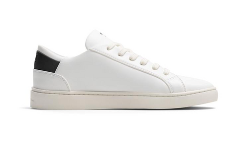 A white casual sneaker with a small black strip at the back.