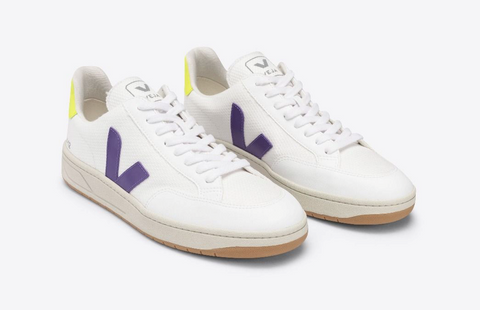 """White casual sneakers with a violet """"V"""" shaped accent mark on the arch and outer side."""