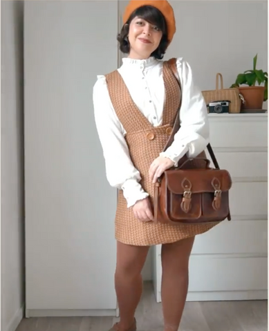 A woman in a brown dress and white sweater, holding a brown satchel bag.