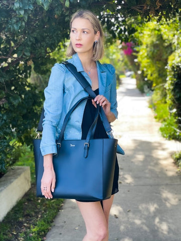 A blonde woman in a black dress and blue jacket holds a navy blue tote bag over one shoulder.