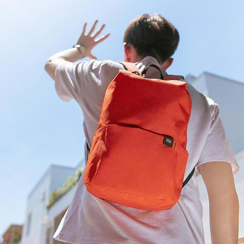 a guy carrying a small orange backpack