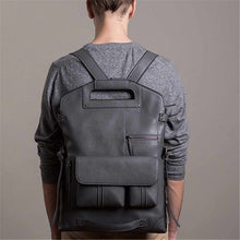 Load image into Gallery viewer, a guy carrying a grey vintage leather backpack