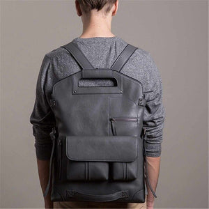 a guy carrying a grey vintage leather backpack