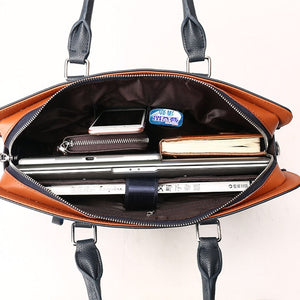 the internal pocket of a leather briefcase full with a laptop, a mobile phone, and an agenda