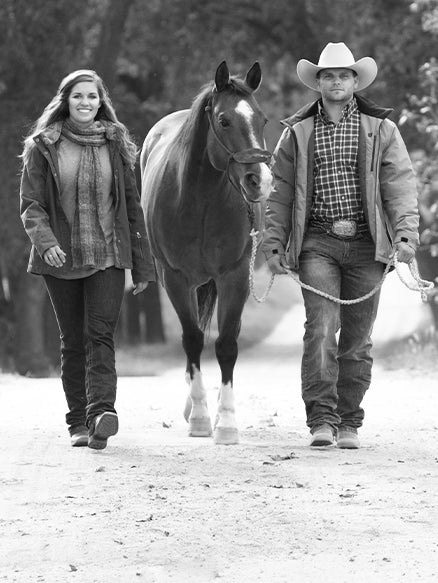 Couple walking with their horse in the middle.