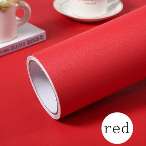 red wallpaper roll on table