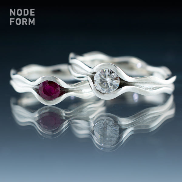 Ruby and moissanite platinum wave engagement rings