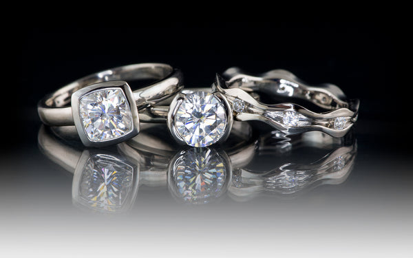 Cushion and round moissanite engagement rings by Nodeform