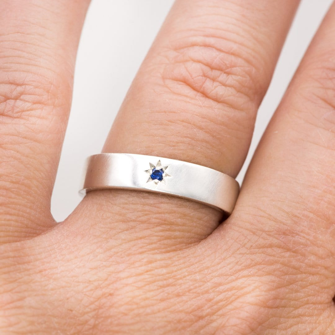 It is an image of Flat Wedding Band with Star Set Blue Sapphire
