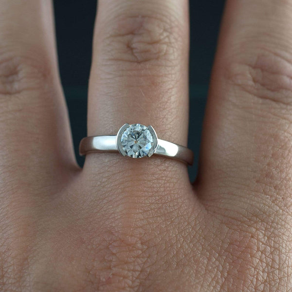 6mm round forever brilliant moissanite half bezel solitaire engagement ring on hand