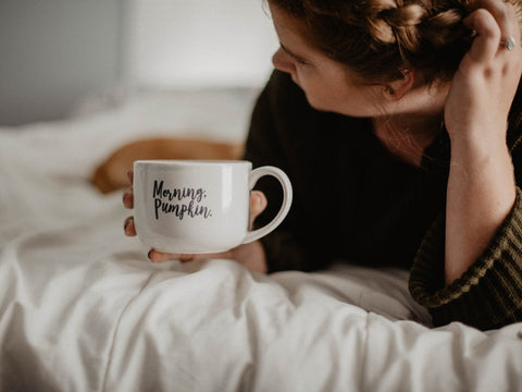 in bed with a cup of coffee