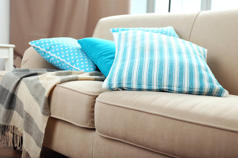 Image of beige couch with teal throw pillows and a striped throw blanket