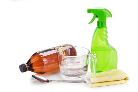 A spray bottle, measuring cup, cleaning rag, vinegar container and spoon stand in front of a white background