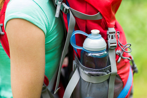 A plastic, reusable water bottle sits in a backpack pocket of a woman hiking