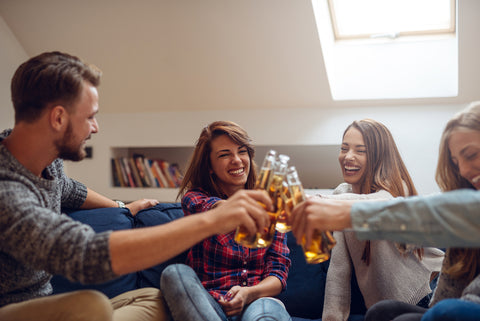 Group of friends clinking with beer and having a good time in the apartment