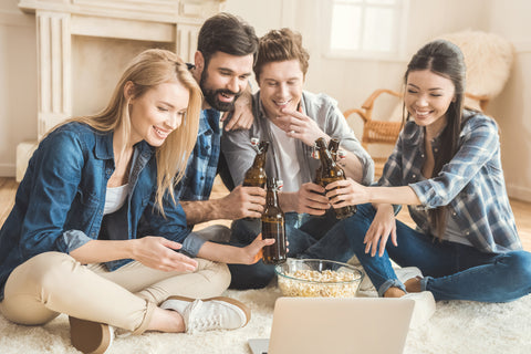 Two young couples watching movie on laptop while drinking beer and eating popcorn