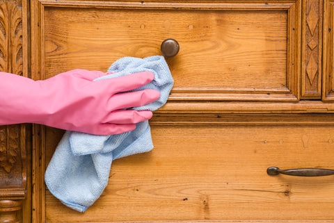 How Often Should I Vacuum My Dorm? cleaning with pink gloves and microfiber cloth