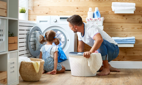 Happy father and daughter doing laundry with washing machine