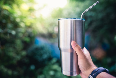 A man's hand holds a stainless steel coffee tumbler outdoors