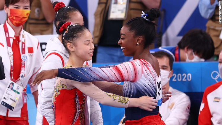 Biles and Guan embrace during the balance beam final