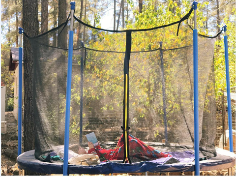 A kid enjoy reading on a Zupapa 15 ft. trampoline
