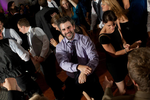 A wedding guest dancing happily with his hands in front of him.