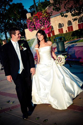 Mike and Jenna on their wedding day walking on a path looking happy and excited.