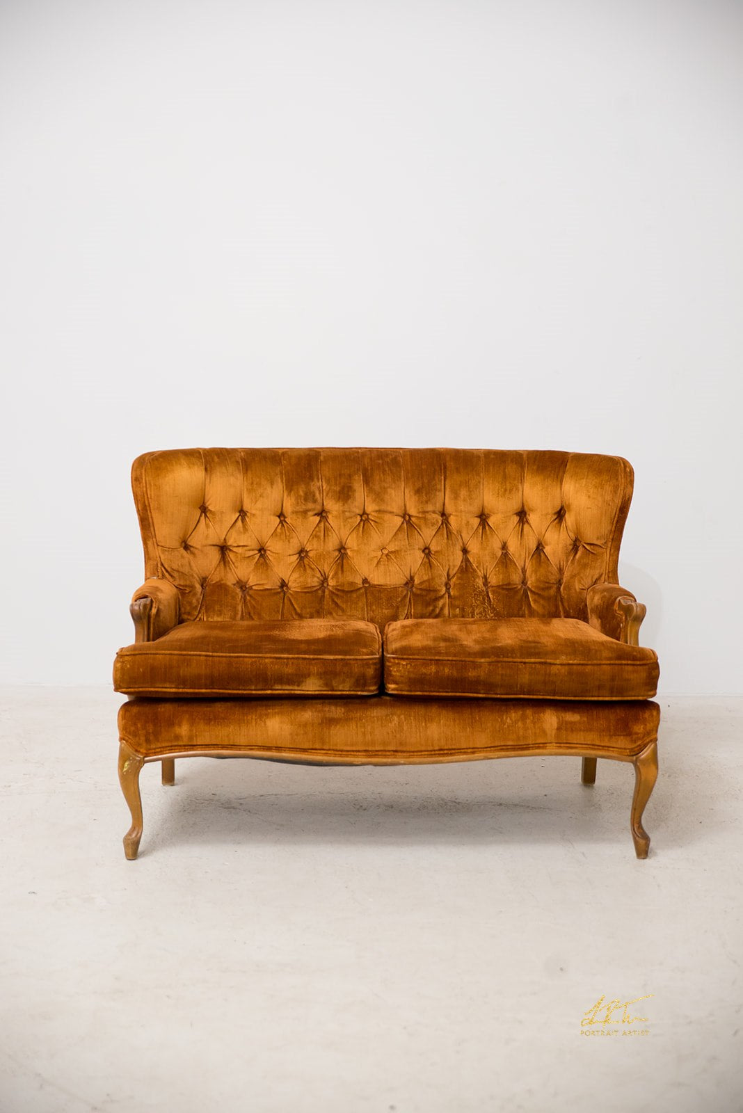 Pumpkin orange or gold tufted, antique love seat for rent.