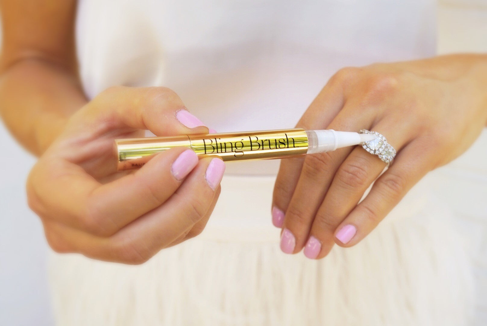 A close-up photo of a woman with pretty pink nails is using the Baublerella Bling Brush to clean her large diamond ring.