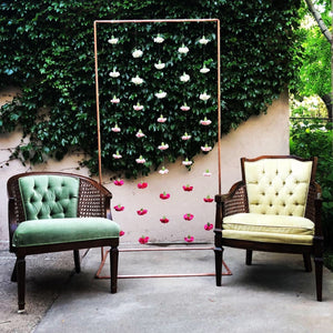 Pink and white carnation flowers hanging from a 6ft by 3ft copper arch. On the left of the backdrop is a green vintage chair. On the right of the backdrop is a yellow-ish velvet vintage chair.
