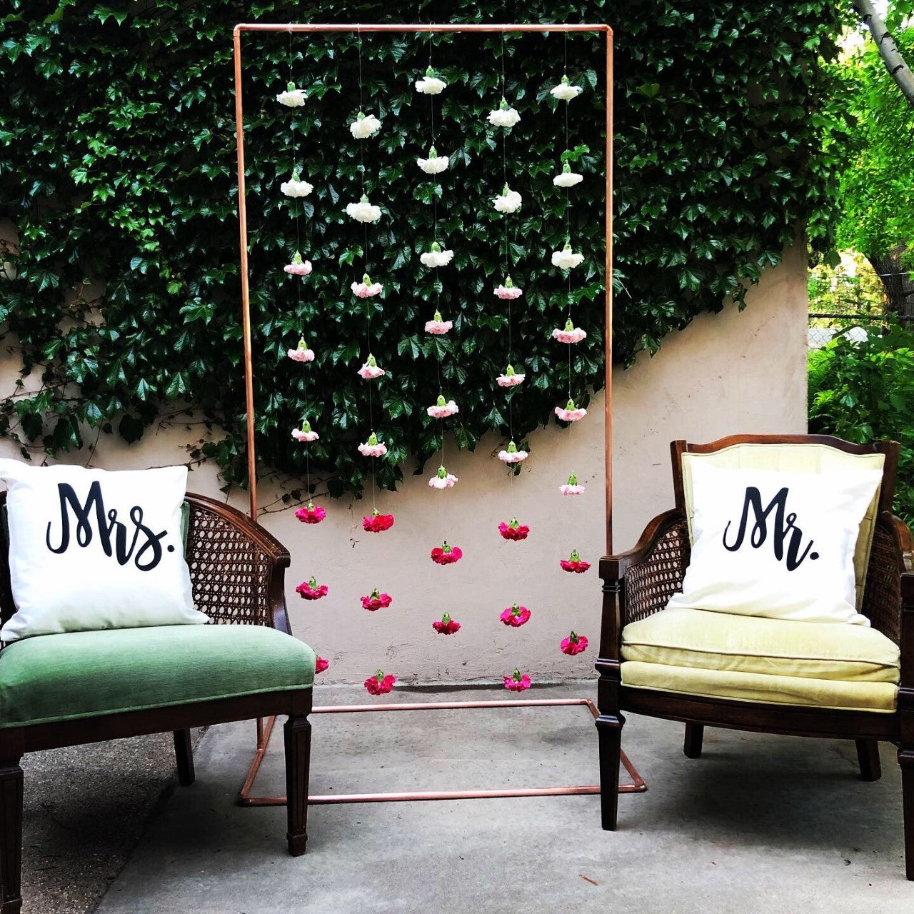 "Pink and white carnation flowers hanging from a 6ft by 3ft copper arch. On the left of the backdrop is a green vintage chair with a white pillow that says ""Mrs."" in black cursive. On the right of the backdrop is a yellow-ish vintage chair with a white pillow that says ""Mr."" in black cursive."