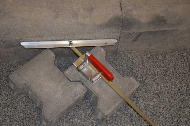 Angle Scribe tool that guides cutting pavers up against a sitting or vertical wall