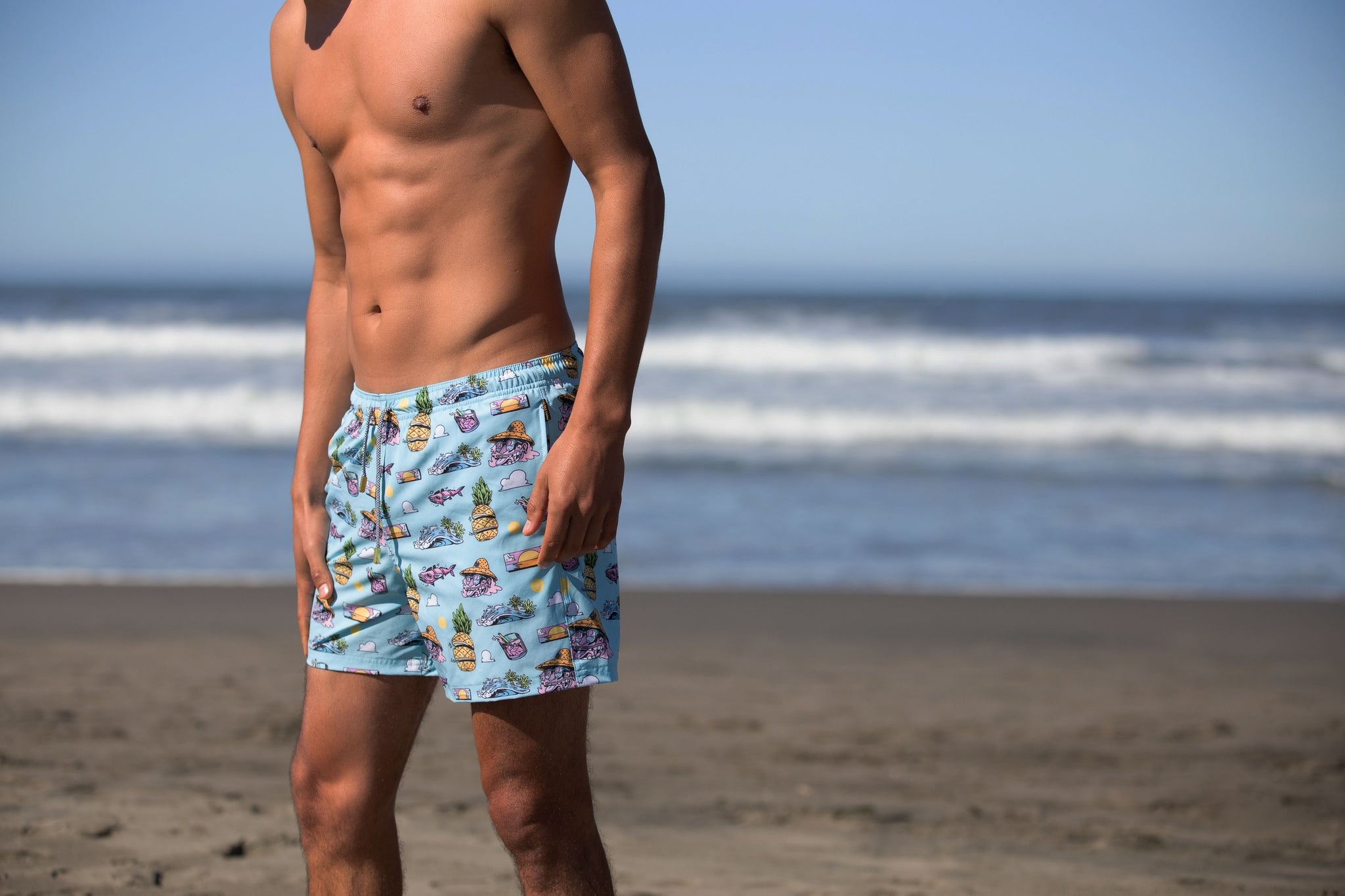 side view of men at beach wearing tropical swim trunk