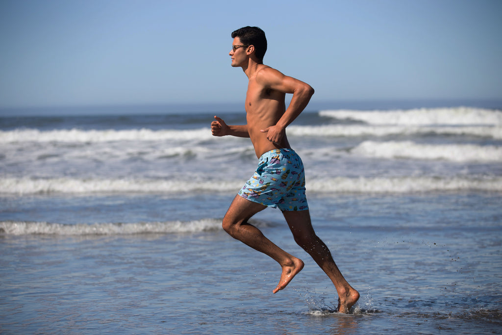 model running in the beach with swim trunk