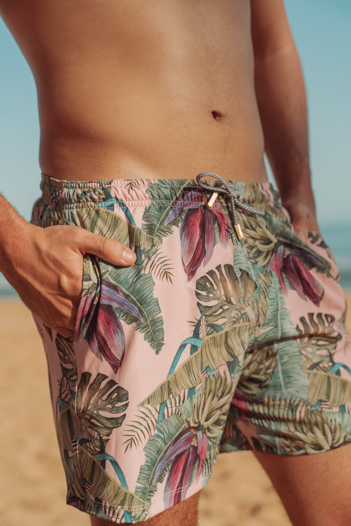 Male model torso shirtless with hand in pocket of the swim trunk with a beach background