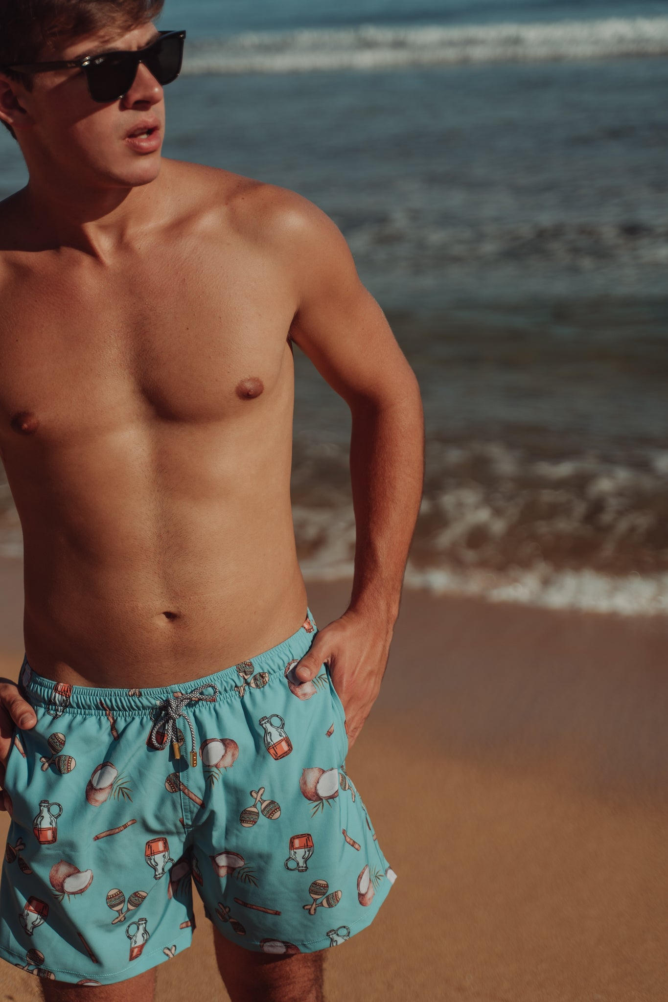 Shirtless model with a beach background wearing sustainable swimsuit for men with a tropical print