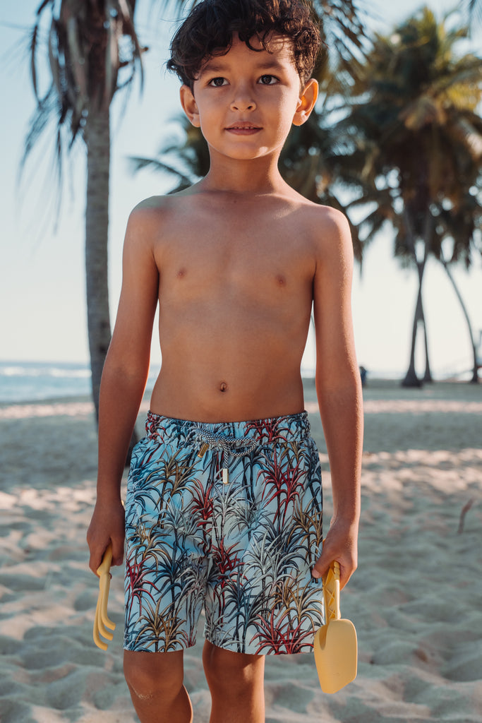 Child wearing sugarcane print swim trunk with a sandy beach background