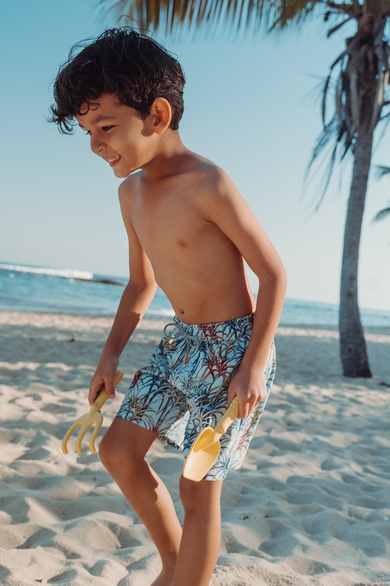 Side standing kid wearing sugar cane print swim trunk with ocean and beach background