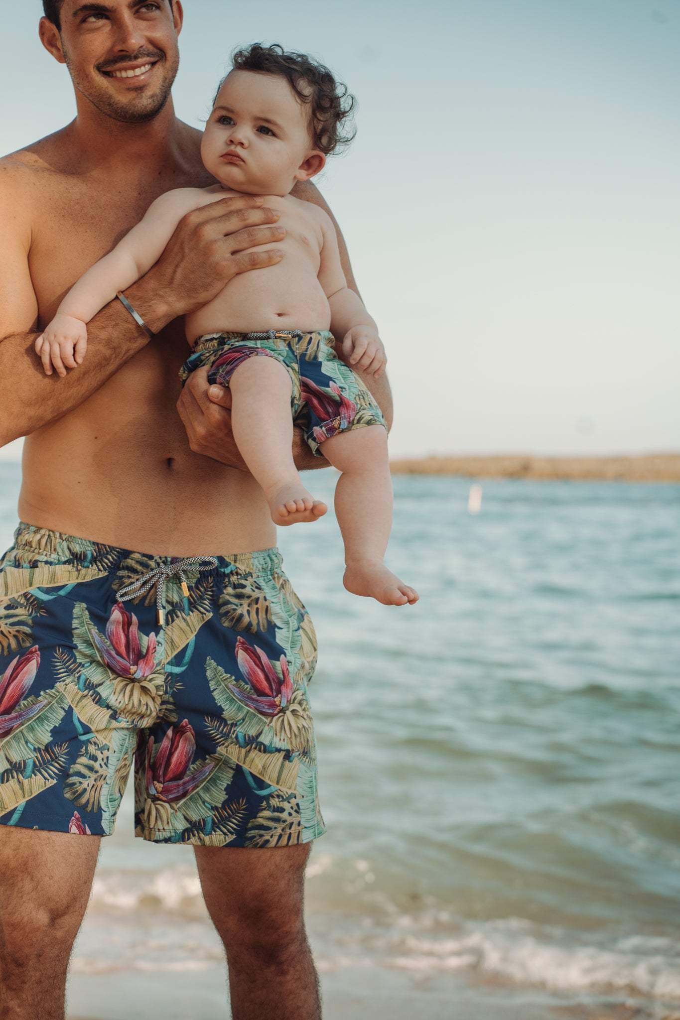 Model adult holding a baby both wearing swim trunk with the ocean background